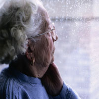 Photo: An elderly woman looking out of a window