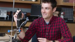 Image: man touching a prosthetic hand equipped with the e-dermis; Copyright: Larry Canner/JHU