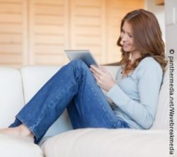 Photo: Woman sitting on the sofa, reading an e-book; © panthermedia.net/wavebreakmedia