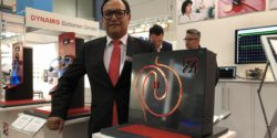 Image: Man presents a sensor at a trade fair stand; Copyright: beta-web/Schlüter