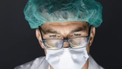 Image: Surgeon who wears a face mask and is illuminated from below; Copyright: SCHOTT AG