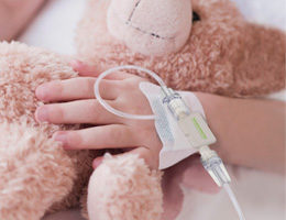 Image: Child hand with infusion holding a teddy bear