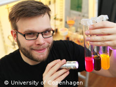 Photo: Young scientist smiles and shows vials of colorful fl