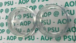 Image: two plastic domes, one with the new coating, one without; Copyright: Giebink Lab/Penn State