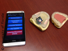 Photo: Smart phone next to false teeth and mouth guard