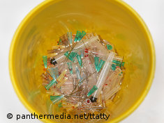 Photo: Used syringes in a yellow bucket