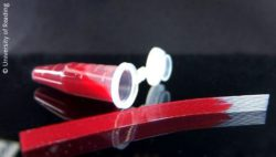 Image: A small vial filled with blood. In front of it lies a microfluidic strip with blood; Copyright: University of Reading