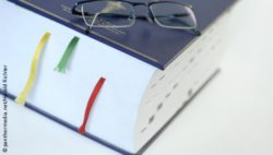 Photo: Glasses lying on a thick book