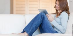 Photo: Young woman sits on the couch and uses a tablet; Copyright: panthermedia.net/Wavebreakmedia