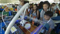Photo: People look at a 3-D printer