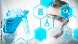 Image: Laboratory technician in a white coat and glasses holding up a test tube - a blue graphic with chimical symbols and signs is laid over it; Copyright: PantherMedia / mikkolem