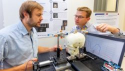 Image: Two men are working with a model of the human skull in the lab; Copyright: WHZ/Helge Gerischer