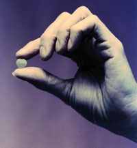 Photo: A hand holding a pill