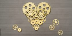 Image: Gear wheels forming a heart on a table from above; Copyright: panthermedia.net/pogonici