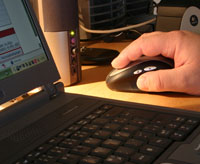 Photo: A hand at a computer mouse besides a laptop