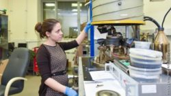 Image: a woman in a nice dress stands at a large industry machine to produce nanofibre; Copyright: Sergey Gnuskov/NUST MISIS