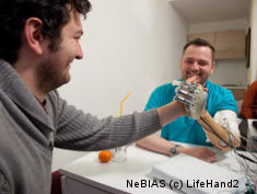 Photo: Two men at arm wrestling, one wearing a prosthesis