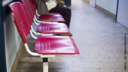 Picture: a row of red metal chairs in a corridor, on the last one sees a person sitting blurred; Copyright: panthermedia.net/trybex