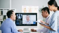 Image: three persons around a computer showing a video call with a physician and radiological images of a chest; Copyright: PantherMedia/DragonImages