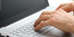 Photo: Man is typing on his netbook; copyright: panthermedia.net/Ronalds Stikans