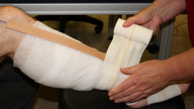 Photograph of the in-vivo sub-bandage pressure measurement. The sensor array sits on top of the first layer, while the compression bandage was being applied
