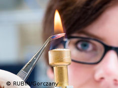 Photo: Woman holding forceps in a flame