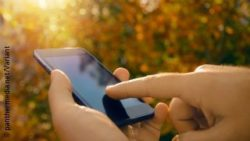 Image: close-up of hands on a smartphone, in the background you can see autumn leaves; Copyright: panthermedia.net/Variant